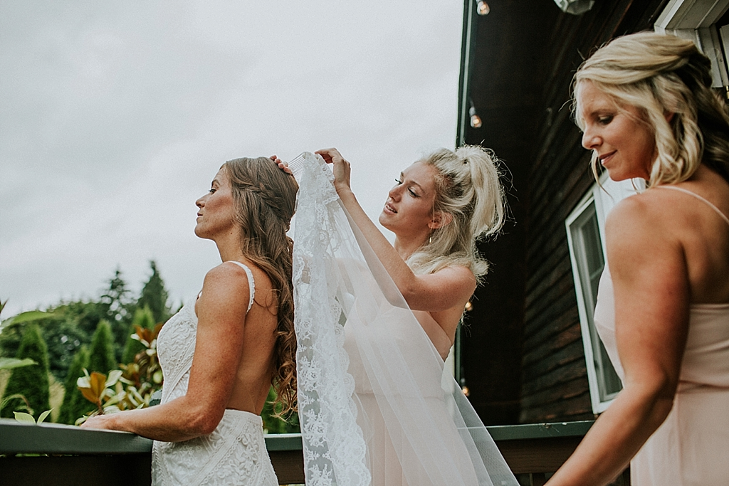 bride having her veil put on by her bridesmaids