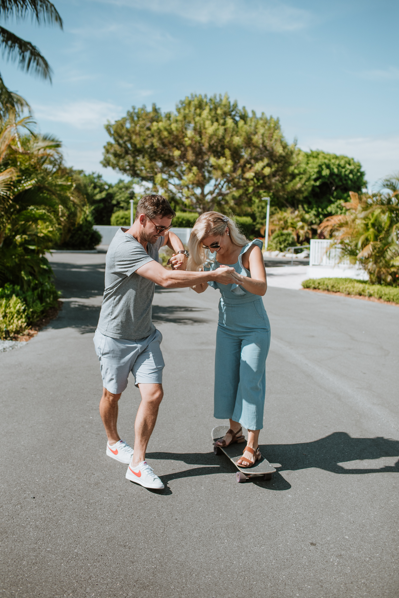 Fun couple skateboarding during their engagement shoot