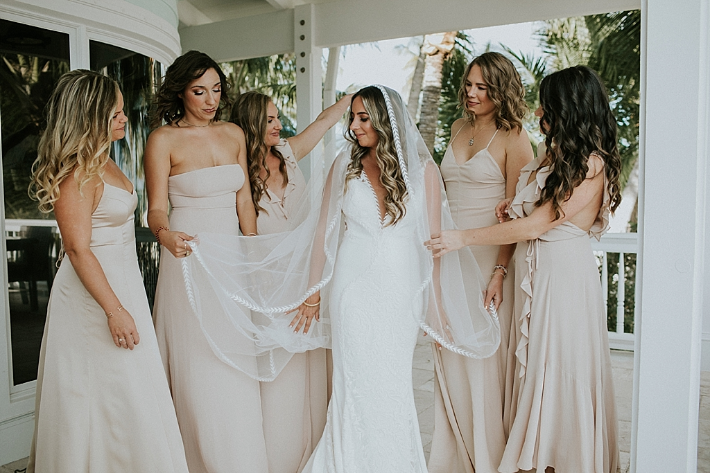 bridesmaids helping a bride getting dressed for her wedding day in the keys