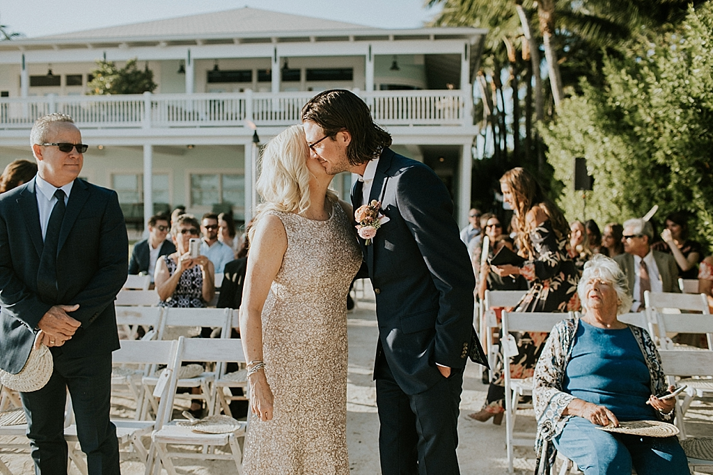 a groom embraces his mom as he walks down the isle